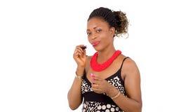 Portrait de la jeune femme africaine mettant le rouge à lèvres images libres de droits