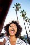 Portrait de la jeune femme africaine riant dehors avec les cheveux bouclés photographie stock