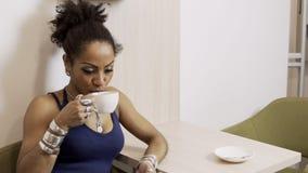 Portrait de la jeune femme afro-américaine qui boit du café dans le café banque de vidéos