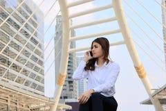 Portrait de la jeune femme asiatique attirante d'affaires parlant au téléphone intelligent mobile à l'arrière-plan de bâtiment de Image libre de droits