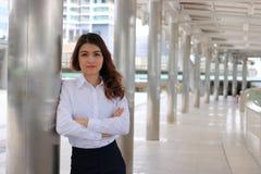 Portrait de la jeune femme asiatique attirante d'affaires se penchant un poteau à l'arrière-plan urbain de bâtiment photos stock