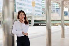 Portrait de la jeune femme asiatique attirante d'affaires se tenant et regardant loin la ville Images libres de droits