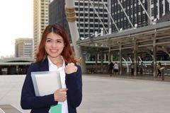 Portrait de la jeune femme asiatique réussie d'affaires se tenant et semblant sûre sur le fond urbain Photos stock