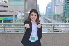 Portrait de la jeune femme asiatique réussie d'affaires semblant sûre et souriant au fond urbain de ville Photos libres de droits