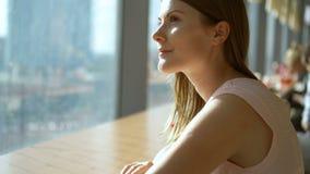 Portrait de la jeune femme assez rêveuse s'asseyant à la table en café près de la pensée de fenêtre Mail de l'espace restauration banque de vidéos