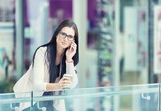 Portrait de la jeune femme attirante d'affaires se tenant dans le centre commercial avec du café et à l'aide de son téléphone por Photos stock
