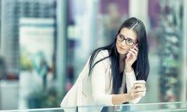 Portrait de la jeune femme attirante d'affaires se tenant dans le centre commercial avec du café et à l'aide de son téléphone por Images stock