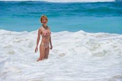 Portrait de la jeune femme attirante et heureuse dans le bikini posant à stupéfier la belle plage de désert avec de grandes vague photos stock