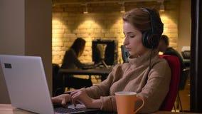 Portrait de la jeune femme aux cheveux courts dans des écouteurs dactylographiant attentivement sur l'ordinateur portable et la b banque de vidéos