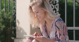 Portrait de la jeune femme blonde à l'aide du comprimé banque de vidéos