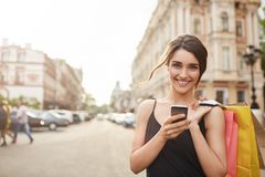 Portrait de la jeune femme caucasienne attirante gaie avec les cheveux foncés dans la robe noire souriant in camera avec des dent Photo stock