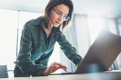 Portrait de la jeune femme d'affaires belle ? l'aide de l'ordinateur portable au bureau moderne Fond brouill? image stock