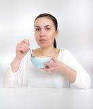 Portrait de la jeune femme dans les sous-vêtements mangeant des céréales Jeune femme mangeant la mousseline de céréale (flocons) image stock