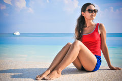 Portrait de la jeune femme de regard asiatique s'asseyant près de la piscine à la plage tropicale chez les Maldives Photos stock