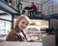 Portrait de la jeune femme de sourire à l'aide de la tablette en café images libres de droits