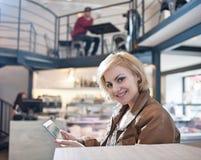 Portrait de la jeune femme de sourire à l'aide de la tablette en café photos libres de droits