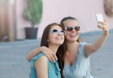 Portrait de la jeune femme deux positive ayant l'amusement et faisant le selfie Photographie stock