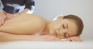 Portrait de la jeune femme en bonne santé avec la peau de porcelaine se reposant pendant le massage dans le salon de station ther banque de vidéos