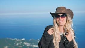 Portrait de la jeune femme européenne d'élégance dans le chapeau de cowboy et des lunettes de soleil souriant et flirtant banque de vidéos