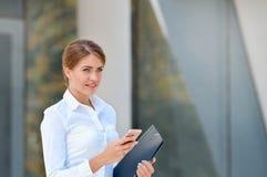 Portrait de la jeune femme gaie à l'aide du smartphone dehors images libres de droits