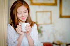 Portrait de la jeune femme magnifique de brune tenant la tasse Photo libre de droits