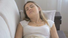 Portrait de la jeune femme malade s'asseyant sur le sofa et la toux clips vidéos