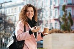 Portrait de la jeune femme mignonne à l'aide du téléphone portable dans la rue Photos stock