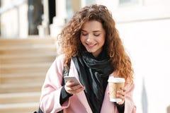 Portrait de la jeune femme mignonne à l'aide du téléphone portable dans la rue Photo libre de droits