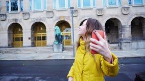 Portrait de la jeune femme mignonne qui parle dans l'appel visuel utilisant le mobile Image libre de droits