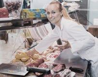 Portrait de la jeune femme positive travaillant dans la boucherie Photos libres de droits