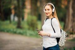 Portrait de la jeune fille attirante à l'arrière-plan urbain écoutant la musique avec des écouteurs Images stock
