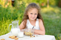 Portrait de la jeune fille ayant le petit déjeuner et le lait boisson extérieurs Céréale, mode de vie sain photographie stock
