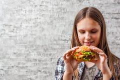 Portrait de la jeune fille de brune d'adolescent avec de longs cheveux mangeant l'hamburger Fille essayant de manger des aliments image libre de droits