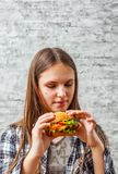 Portrait de la jeune fille de brune d'adolescent avec de longs cheveux mangeant l'hamburger Fille essayant de manger des aliments photo stock