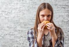 Portrait de la jeune fille de brune d'adolescent avec de longs cheveux mangeant l'hamburger Fille essayant de manger des aliments photo libre de droits