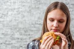Portrait de la jeune fille de brune d'adolescent avec de longs cheveux mangeant l'hamburger Fille essayant de manger des aliments photographie stock