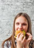 Portrait de la jeune fille de brune d'adolescent avec de longs cheveux mangeant l'hamburger Fille essayant de manger des aliments images stock
