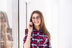 Portrait de la jeune fille caucasienne de sourire attirante parlant par téléphone portable Images stock