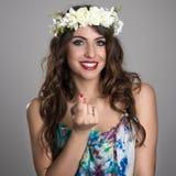 Portrait de la jeune fille féerique avec la guirlande de fleur souriant avec le geste de invitation de doigt Photos libres de droits
