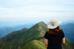 Portrait de la jeune fille de hippie utilisant le T-shirt noir et le chapeau beige tournant le dos à la caméra photo stock