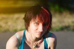 Portrait de la jeune fille de planchiste se reposant en parc, dehors Cheveux rouges Photographie stock