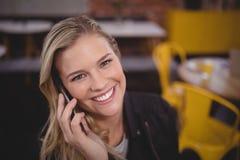 Portrait de la jeune jolie femme de sourire écoutant le smartphone photo libre de droits
