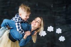 Portrait de la jeune mère affectueuse jouant avec son enfant Femme espiègle tenant le petit fils mignon au-dessus de sa tête Images libres de droits
