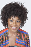 Portrait de la jolie femme d'Afro-américain dans l'usage traditionnel souriant au-dessus du fond gris images libres de droits