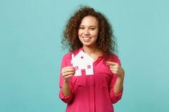 Portrait de la jolie fille africaine dans des vêtements sport roses dirigeant l'index sur la maison de papier d'isolement sur la  image stock