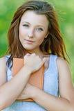 Portrait de la jolie fille de sourire tenant le livre photo stock