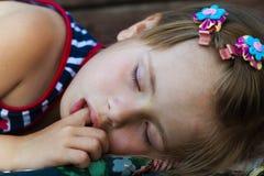 Portrait de la jolie fille de sommeil d'enfant qui suce son doigt tout en dormant photographie stock libre de droits