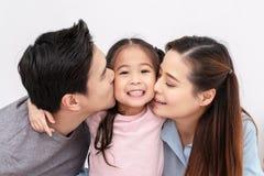 Portrait de la joue de baiser de famille asiatique attirante ensemble étroite sur le fond blanc d'isolement de studio Alpha et mi photographie stock libre de droits