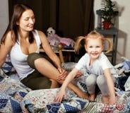 Portrait de la mère et de la fille s'étendant dans la lecture de lit et l'écriture, concept de personnes de mode de vie Photo stock