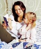 Portrait de la mère et de la fille s'étendant dans la lecture et le writi de lit Photos stock